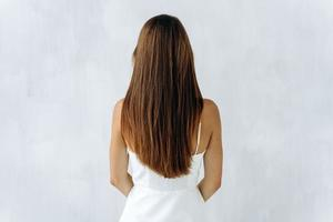 Beauty and hair care. Back view of young sensual brunette lady with voluminous hair posing isolated on white and showing her healthy hair. Stock photo