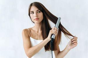 portarretrato retrato de una mujer joven sonriente en ropa doméstica con una plancha de pelo mientras se prepara para caminar. concepto de estilo de vida en casa foto