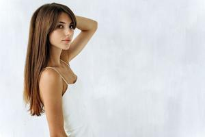 Cintura para arriba retrato de chica atractiva con cabello castaño largo y recto mirando a cámara con expresión seria. Copie el espacio en el lado izquierdo. concepto de apariencia de mujer foto