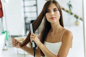 nuevo estilo de cabello. Mujer joven alegre que se siente segura y sonriente mientras sostiene una plancha favorecedora y alisa su cabello sano foto