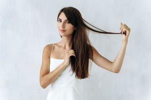 Cintura para arriba retrato de la mujer caucásica de pelo largo poniendo sus manos en su cabello y jugando con él mientras posa con una pared blanca en el fondo foto