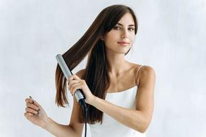 cintura para arriba retrato de la mujer joven contenta con una plancha de pelo en el baño mientras mira a la cámara con una sonrisa de placer. concepto de apariencia de mujer foto