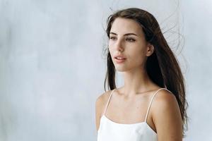 piel perfecta. cintura para arriba retrato de mujer joven sensual mirando a otro lado suavemente. aislado sobre fondo blanco. apariencia de mujer y concepto de cuidado de la piel foto