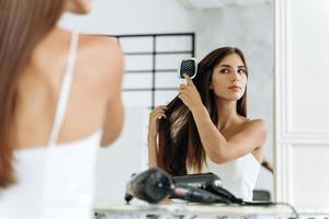 peinado y cuidado diario del cabello en casa. Alegre dama caucásica milenaria peinando largo y hermoso cabello lacio en el interior del baño en la mañana foto