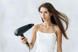 Retrato de mujer alegre que sopla el viento en el cabello después de tomar una ducha. ella mirando a la cámara con expresión tranquila. concepto de apariencia de mujer foto
