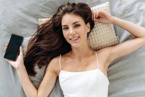 feliz hermosa joven despierta después de un sueño saludable y acostada con su teléfono inteligente en una cómoda cama acogedora. Señora sonriente despertando y disfrutando de buenos días. foto