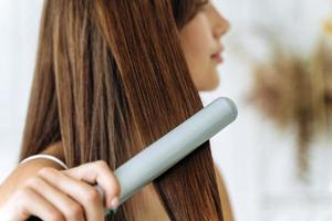 Hairdressing. Woman with beautiful long straight hair using hair straightener. Gorgeous girl straightening healthy hair with flat iron. Hair ironing and hairstyle concept photo