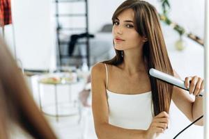 hermosa joven sonriente con una plancha de pelo mientras mira en el espejo en el baño. chica segura mirando su reflejo con sonrisa de placer foto