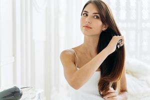 Calm young lady in domestic clothes combing hair and looking away while started her morning from the beauty routine. Stock photo