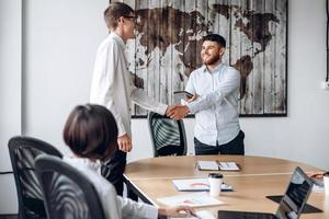 A smiling bearded boy shakes his colleague's hand in the office photo