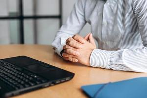 Businessman clasped hands on desk, working on computer photo