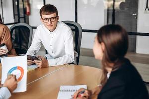 Young man in glasses at business meeting, listening carefully to his colleague photo