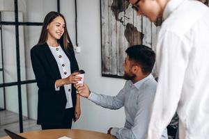 Pretty girl gives a cup of coffee to her boss photo