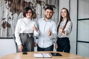 Young team of three showing showing thumb up photo