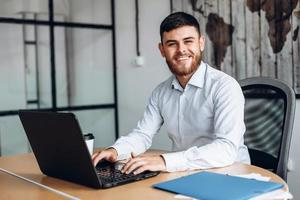 Smiling, bearded man working on computer in office photo