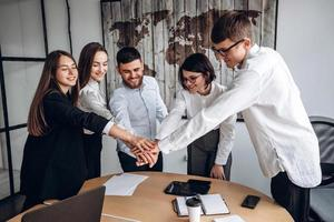 Working together. A friendly team of business people, putting their hands together, is one. photo