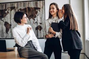 hermosas mujeres empresarias discuten y susurran entre sí foto