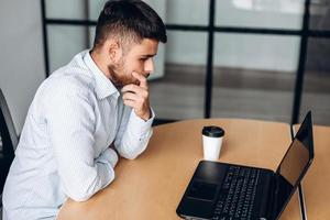 A bearded man in a shirt thinks intently while working in the office photo