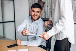 Smiling man with beard, works in office, looks at important documents and signs them photo
