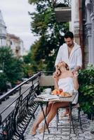mujer embarazada con su marido en el balcón se reúnen en la mañana foto