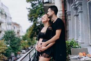 Feliz pareja esperando bebé, en ropa negra posando en la terraza, balcón foto