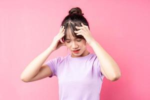 Retrato de niña con dolor de cabeza, aislado sobre fondo rosa foto