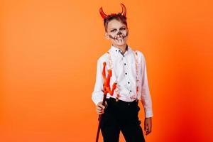 chico diablo de pie media vuelta contra un fondo naranja en maquillaje de mascarada. concepto de halloween foto