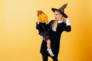 Mujer en traje de mascarada y sombrero posando sobre fondo amarillo sosteniendo niña - imagen foto