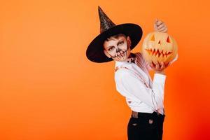Retrato de niño con maquillaje de mascarada de diablo y sombrero mostrando una calabaza. concepto de halloween foto