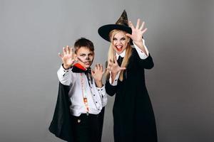Madre e hijo en disfraces mostrando gesto de miedo a la cámara.- Concepto de Halloween foto