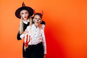 mujer y niño en maquillaje de mascarada de diablo mostrando emoción de asombro. concepto de halloween foto