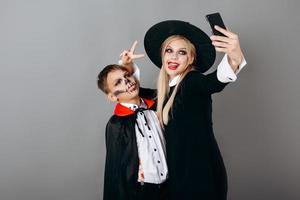 Madre e hijo en disfraces mostrando gesto de victoria y haciendo selfie con fondo de estudio foto
