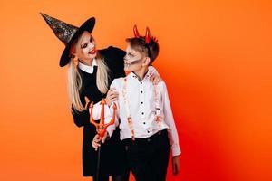 madre y sol en maquillaje de mascarada de diablo mirando el uno al otro. concepto de halloween foto
