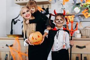 Funny family in the kitchen standing  in fancy dress and looking at the camera - Halloween concept photo