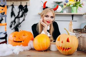 Devil woman sitting at the table next a pumpkins and smiling looking at the camera photo