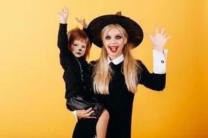 Mujer en traje de mascarada y sombrero posando sosteniendo niña y mirando a la cámara divertida - imagen foto