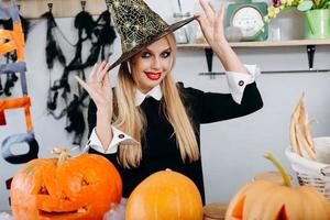 Retrato de mujer feliz toca su sombrero y juguetonamente mirando a la cámara.- Imagen de Halloween foto