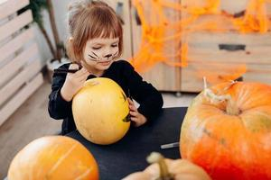 Little girl drawing on pumpkin sitting at the table. - Image photo