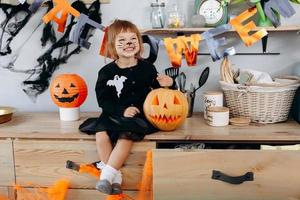 Little funny girl sitting next the pumpkin and happily smiling. - Halloween concept photo