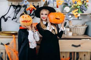 Mother and boy standing  in fancy  dress holding a pumpkin. Boy hide his face- Image photo
