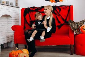 Woman and little girl have a funny time on red sofa. Emotion and Halloween concept photo