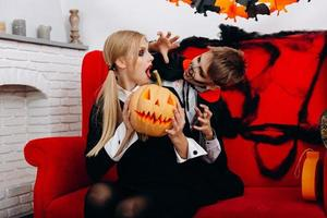 Mother and son have a funny time on red sofa. Boy scary woman.  Halloween concept photo