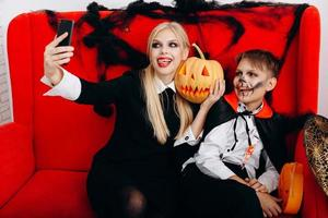 Mother and son have a funny time on red sofa and make a selfie closeup. Emotion and Halloween concept photo