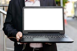 Primer plano de la imagen del empresario sosteniendo la computadora portátil abierta, pantalla en blanco blanca vacía- imagen foto