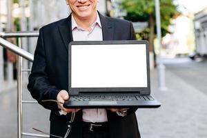Recorte de imagen del empresario sosteniendo portátil abierto, pantalla en blanco en blanco vacío- imagen foto