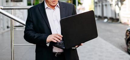Recortando la imagen del empresario senior sosteniendo una computadora portátil en la mano y escribiendo de pie en la ciudad.- imagen foto
