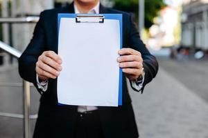Primer plano blanco vacío maqueta en blanco de la hoja de papel en manos masculinas - espacio de copia foto
