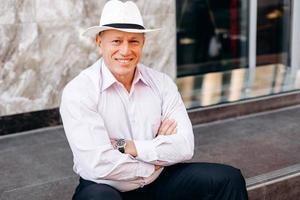 Retrato de hombre mayor en camisa y sombrero sentado en el pavimento con las manos juntas. - imagen foto