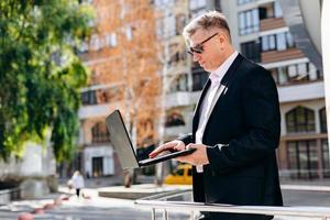 serio empresario senior en gafas de sol sosteniendo una computadora portátil y trabajando en ella al aire libre. - imagen foto