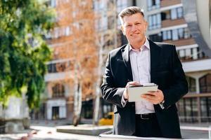 Retrato de hombre de negocios senior feliz escribir una nota y mirando a la cámara. - imagen foto